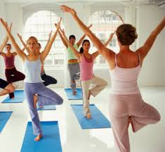 Women in Yoga class doing the tree pose