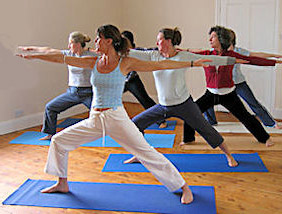 Group attending yoga class in the warrior pose